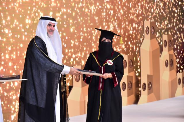 College of Education Dean Dr. Ahmed Al Emadi presents a happy graduate with her diploma